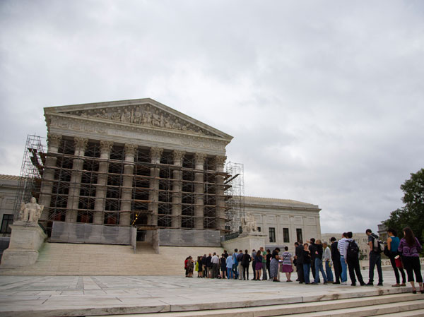 This Oct. 7, 2013 file photo shows people waiting in line to enter the court in Washington. Supreme Court justices are being asked to resolve a new clash of technology and privacy in the digital age. (AP Photo/ Evan Vucci, File)