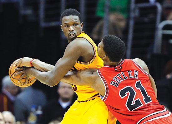 Chicago Bulls' Jimmy Butler (21) tries to poke the ball away from Cleveland Cavaliers' Luol Deng in an NBA game Wednesday in Cleveland. (AP Photo/Mark Duncan)