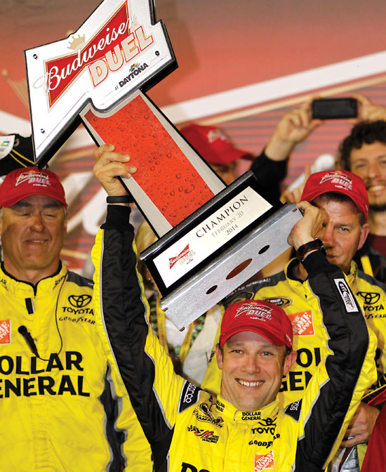 Matt Kenseth raises the trophy in Victory Lane after winning the first of two NASCAR Sprint Cup series qualifying auto races at Daytona International Speedway in Daytona Beach, Fla., Thursday, Feb. 20, 2014. (AP Photo/Terry Renna)