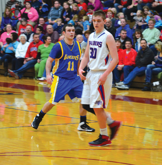 Lincolnview's Kyle Williams (11) and Corbin Linder (30) of Wayne Trace went shot-for-shot as the Raiders out-lasted the Lancers 73-72 on Thursday night. Williams had 22 points to pace the Lancers, while Linder poured in 28 points in the win. (Times Bulletin/John Parent)