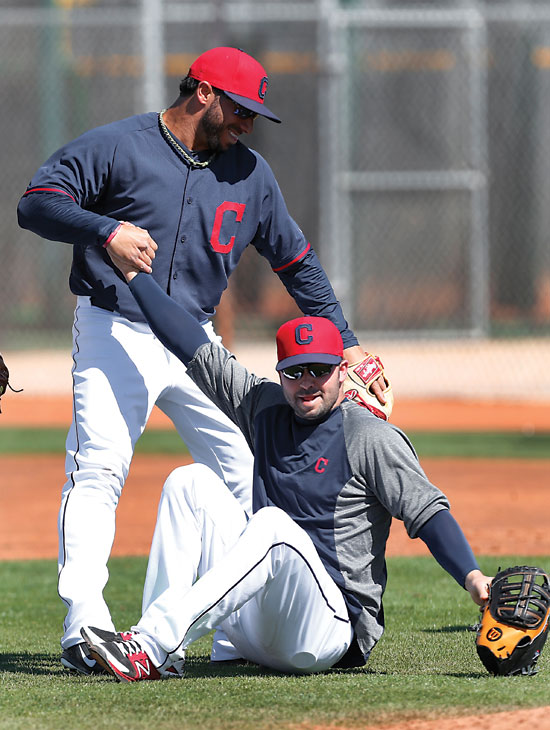 Cleveland Indians' Mike Aviles helps up Nick Swisher during spring training baseball practice in Goodyear, Ariz., Monday, Feb. 24, 2014. (AP Photo/Paul Sancya)