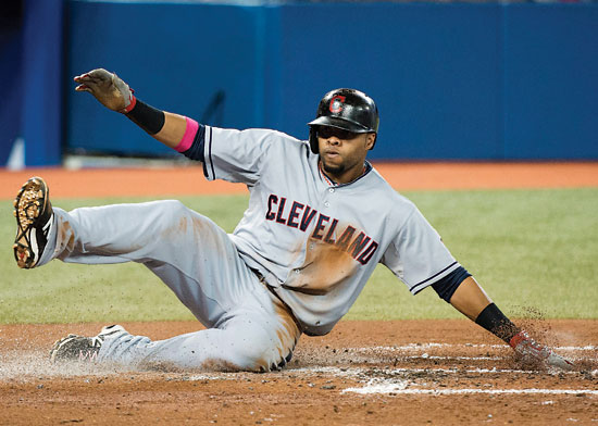 Cleveland Indians' Carlos Santana slides safely into home plate during the second inning of a baseball game against the Toronto Blue Jays on Wednesday, May 14, 2014, in Toronto. (AP Photo/The Canadian Press, Nathan Denette)