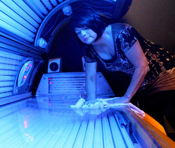 In this April 2, 2014 file photo, Teresa Lynch, owner of Dynamic Tanning in DeKalb, Ill., wipes down a tanning bed. (AP Photo/Daily Chronicle, Monica Maschak, File)