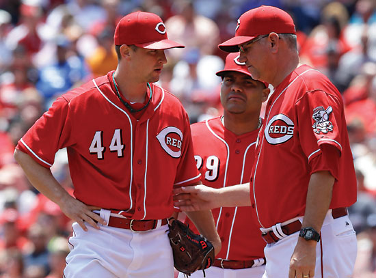 Cincinnati Reds starting pitcher Mike Leake (44) talks with pitching coach Jeff Pico, right, as first baseman Brayan Pena listens in, during the fourth inning of a baseball game against the San Francisco Giants, Thursday, June 5, 2014, in Cincinnati. (AP Photo/Al Behrman)