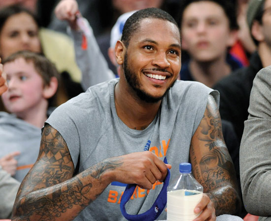 In this Jan. 24, 2014 file photo, New York Knicks' Carmelo Anthony smiles as he watches from the bench during the fourth quarter of an NBA basketball game against the Charlotte Bobcats, at Madison Square Garden in New York. Signing day has arrived in the NBA, if the biggest free agents care to grab their pens. But it's unclear if Anthony, Chris Bosh and Dwyane Wade _ who all might be waiting on LeBron James to go first _ are ready. (AP Photo/Bill Kostroun, File)