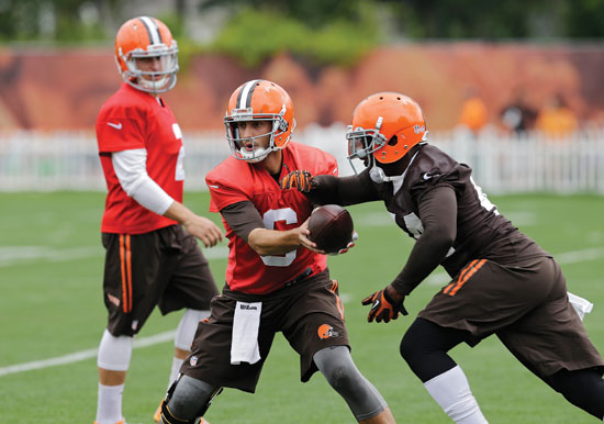Cleveland Browns quarterback Brian Hoyer, center, hands off to running back Ben Tate as quarterback Johnny Manziel watches, back left, during practice at the NFL football team's facility in Berea, Ohio Wednesday, Aug. 20, 2014. Earlier Hoyer was named the opening day starter. (AP Photo/Mark Duncan)