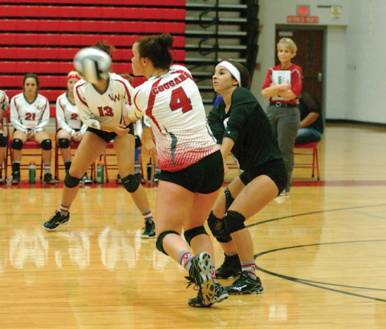 McKenzie Collins (4) and Riley Jones converge to return a serve during Van Wert's match against Ottoville on Tuesday. The Cougars won in three sets. (DHI Media/Tina Eley)