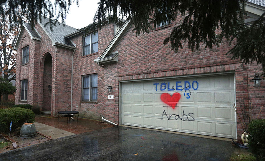 "FILE – This Jan. 12, 2017, file photo, shows a heart and the word ""Toledo"" that Souheir Eltatawy says her daughter painted, covers a swastika and graffiti cursing Arabs that a vandal had spray-painted two days before on the garage door of the Lebanese family's home in the Toledo, Ohio, suburb of Sylvania Township, Ohio. Sylvania Township, Ohio, police say in a Tuesday, Feb. 14, 2017, court filing, that Osama Nazzal, of Toledo, Ohio, is being charged with a second-degree misdemeanor count of criminal damaging the home. (Dave Zapotosky/The Blade via AP, File)"