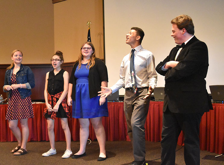 Dru Johnson, second from right, leads a cheer with those in attendance at the Van Wert City Schools Board of Education meeting on Wednesday afternoon at the Niswonger Performing Arts Center Lecture Hall. (DHI Media/Erin Cox)