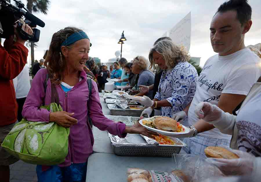 In this Nov. 5, 2014, file photo, members of the homeless community are served meals by advocates in Fort Lauderdale, Fla. Volunteers who feed the homeless in public places say they're providing a needed service. But city governments and some advocates say their well-meaning efforts can hinder long-term solutions and raise sanitation concerns. (AP Photo/Lynne Sladky, File)