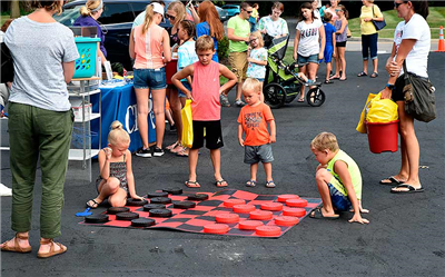 Children gather to play with the lawn checkers game during the Healthy Block Party on Westwood Drive Thursday afternoon. (DHI Media/Sherry Missler)