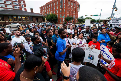 Protesters in the shooting death of Botham Jean, gather at the Jack Evans Police Headquarters, Monday, Sept. 10, 2018 in Dallas. Jean was shot Thursday by off-duty Dallas police officer Amber Guyger, who says she mistook his apartment for hers. (Shaban Athuman /The Dallas Morning News via AP)