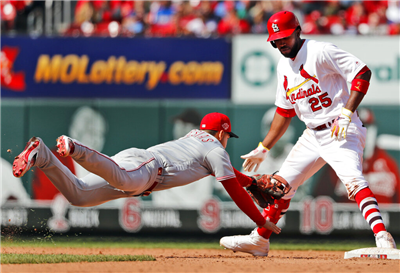 Cincinnati Reds shortstop Jose Iglesias, left, dives to tag out St. Louis Cardinals' Dexter Fowler (25) when Fowler's foot came off the bag after hitting an RBI-double during the eighth inning of a baseball game Sunday, April 28, 2019, in St. Louis. (AP Photo/Jeff Roberson)