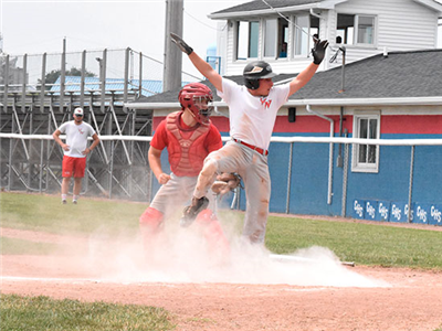 Kaiden Bates of Van Wert looks to the umpire for a call after sliding into home on Sunday. Jefferson catcher J.T. Taviano made the tag but was too late as Bates scored. (DHI Media/Joe Dray)