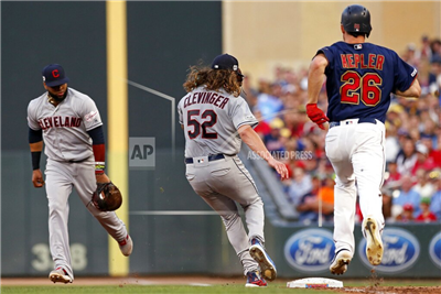 Cleveland Indians pitcher Mike Clevinger, center, beats Minnesota Twins' Max Kepler, right, to first base for the out after Indians first baseman Carlos Santana fielded Kepler's grounder during the third inning of a baseball game Thursday, Aug. 8, 2019, in Minneapolis. (AP Photo/Jim Mone)