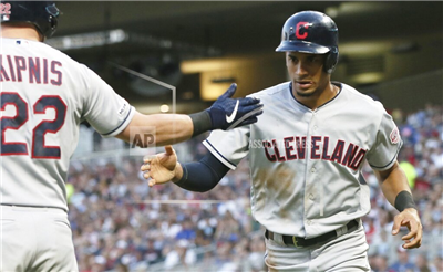 Cleveland Indians' Jason Kipnis, left, congratulates Oscar Mercado, who scored on a single by Jose Ramirez off Minnesota Twins pitcher Kyle Gibson during the fourth inning of a baseball game Thursday, Aug. 8, 2019, in Minneapolis. (AP Photo/Jim Mone)