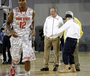 Marquette coach Buzz Williams, right, points to condensation on the court as he talks with Ohio State coach Thad Matta, center, as military personnel and volunteers wipe off the condensation in an attempt to dry the damp court before the start of the Carrier Classic NCAA college basketball game aboard the USS Yorktown in Mount Pleasant, S.C., Friday, Nov. 9, 2012. Officials called off the game because of the damp court. (AP Photo/Mic Smith)