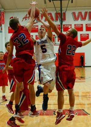 Crestview's Cam Etzler drives the lane between a pair of Wayne Trace defenders in the championship game of the Van Wert Hospital Tip-Off Tournament Saturday. The Knights won the contest 60-40. (Times Bulletin/Tina Eley)