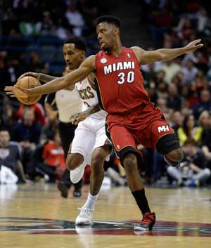 Milwaukee Bucks' Brandon Jennings, left, tries to drive past Miami Heat's Norris Cole (30) during the second half of Game 3 in their first-round NBA basketball playoff series on Thursday, April 25, 2013, in Milwaukee. (AP Photo/Morry Gash)